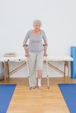 Mujer mayor con las muletas en el gimnasio del hospital Imagen de archivo libre de regalías
