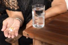 Mujer mayor con las píldoras en su mano y vidrio de agua potable Foto de archivo libre de regalías