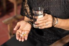 Mujer mayor con las píldoras en su mano y vidrio de agua potable Imagen de archivo