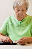Mujer mayor con las tiras de prueba de prueba del azúcar de sangre Imagen de archivo libre de regalías