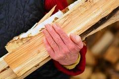 Mujer mayor con leña en las manos en el pueblo Imágenes de archivo libres de regalías