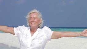 Mujer mayor con los brazos extendidos en la playa hermosa almacen de video