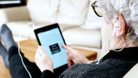 Mujer mayor con los vidrios usando la tableta y auriculares de botón mientras que en el sofá en casa metrajes