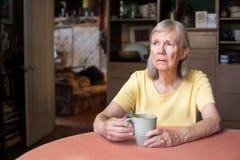Mujer mayor con mirada fija en blanco foto de archivo