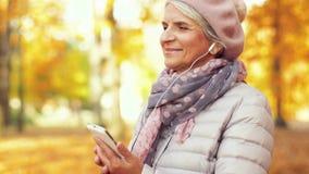 Mujer mayor con smartphone y auriculares en otoño metrajes