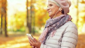 Mujer mayor con smartphone y auriculares en otoño almacen de video