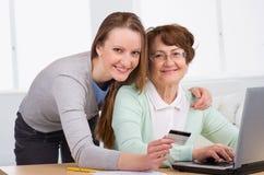 Mujer mayor con su compra en línea de la hija Imagen de archivo