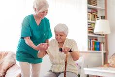 Mujer mayor con su cuidador femenino imagenes de archivo
