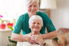 Mujer mayor con su cuidador femenino imagen de archivo