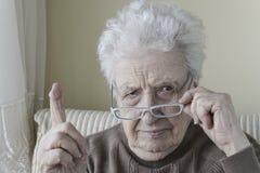 Mujer mayor con su finger para arriba para la advertencia/tener cuidado con Imágenes de archivo libres de regalías