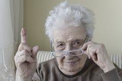 Mujer mayor con su finger para arriba para la advertencia/tener cuidado con Fotografía de archivo libre de regalías