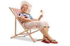 Mujer mayor con un cóctel asentado en una silla de cubierta imágenes de archivo libres de regalías