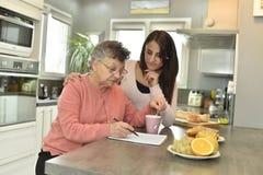 Mujer mayor con un cuidador casero joven en la cocina imagenes de archivo