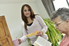 Mujer mayor con un desayuno casero de la porción del cuidador imagenes de archivo