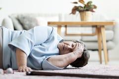 Mujer mayor con un dolor de cabeza después de caer abajo en casa fotografía de archivo libre de regalías
