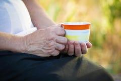 Mujer mayor con una taza de bebida Fotos de archivo libres de regalías