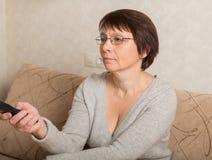 Mujer mayor con una TV teledirigida Imagen de archivo
