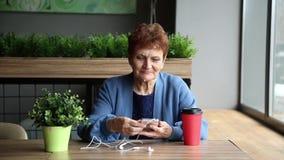 Mujer mayor con una verruga con auriculares y un teléfono almacen de metraje de vídeo