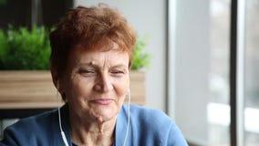 Mujer mayor con una verruga con auriculares y un teléfono almacen de video