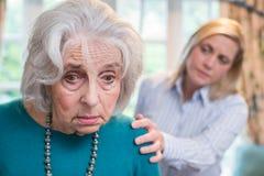 Mujer mayor confusa con la hija adulta en casa imagen de archivo