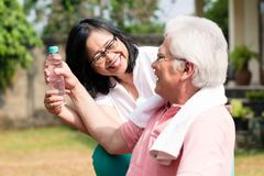 Mujer mayor cuidadosa que da una botella de agua a su socio hacia fuera imagen de archivo