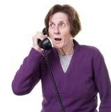 Mujer mayor dada una sacudida eléctrica en el teléfono Imagen de archivo
