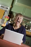 Mujer mayor dada una sacudida eléctrica con un ordenador portátil Imagen de archivo