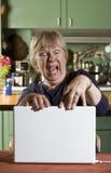 Mujer mayor dada una sacudida eléctrica con un ordenador portátil Foto de archivo