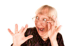 Mujer mayor dada una sacudida eléctrica que mira sobre la tapa de su g Imágenes de archivo libres de regalías