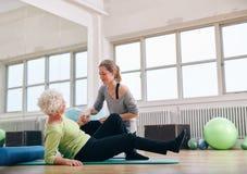 Mujer mayor de ayuda del instructor femenino que se levanta en el gimnasio Foto de archivo libre de regalías