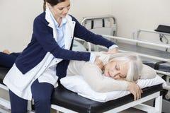 Mujer mayor de Giving Massage To del fisioterapeuta en centro de rehabilitación Imagenes de archivo