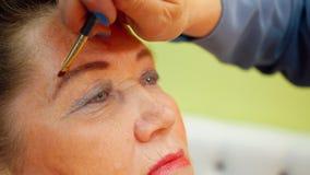 Mujer mayor de la cara mientras que maquillaje de las cejas en cierre del estudio de la belleza para arriba metrajes