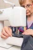 Mujer mayor de la costurera que trabaja en la máquina de coser Fotografía de archivo libre de regalías