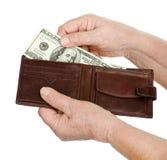 Mujer mayor de la mano con el billete de banco del dólar. Fotografía de archivo libre de regalías