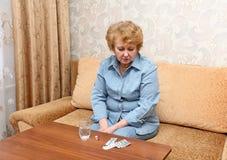 Mujer mayor de la señora con las píldoras de la medicación. Imágenes de archivo libres de regalías