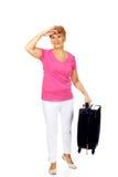 Mujer mayor de la sonrisa con la maleta Foto de archivo libre de regalías