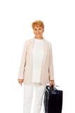 Mujer mayor de la sonrisa con la maleta Fotos de archivo libres de regalías