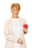 Mujer mayor de la sonrisa que lleva a cabo el modelo del corazón Foto de archivo libre de regalías