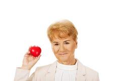 Mujer mayor de la sonrisa que lleva a cabo el modelo del corazón Imagen de archivo libre de regalías