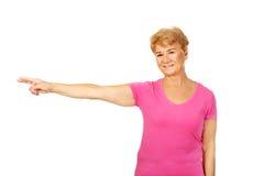 Mujer mayor de la sonrisa que señala para el copyspace o algo Imagenes de archivo