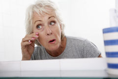 Mujer mayor de los pares que mira la reflexión en el espejo para las muestras del envejecimiento Imagen de archivo libre de regalías