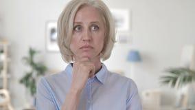 Mujer mayor de pensamiento, inspirándose en oficina metrajes
