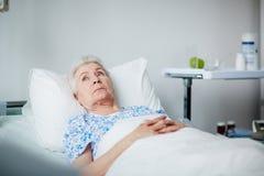 Mujer mayor de reclinación en clínica fotografía de archivo