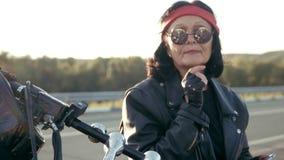 Mujer mayor del motorista en la chaqueta de cuero y guantes que se sientan en su motocicleta fresca La mujer tiene alrededor de v almacen de metraje de vídeo