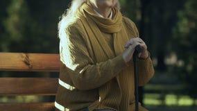 Mujer mayor del trastorno que se sienta con el bastón en el parque, falta de beneficios sociales almacen de video