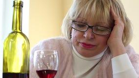 Mujer mayor deprimida que sienta y que mira la botella de vino almacen de metraje de vídeo