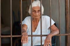 Mujer mayor detrás de barras fotografía de archivo libre de regalías