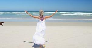 Mujer mayor dichosa que camina en la playa almacen de video