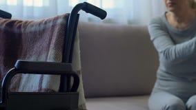 Mujer mayor discapacitada que mira la silla de ruedas y que piensa en problemas de salud almacen de video