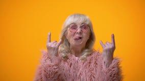 Mujer mayor divertida en la capa rosada que hace gestos del eje de balancín y que muestra la lengua, diversión almacen de metraje de vídeo